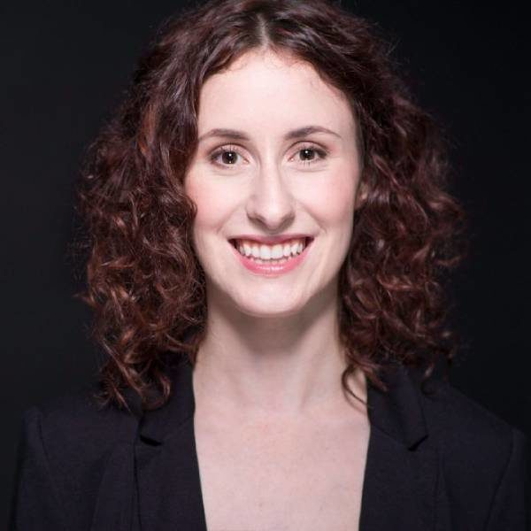 Alethea Bakogeorge, a white disabled woman with dark brown eyes and dark brown curly hair, smiles at the camera. She is wearing a black blazer and is standing against a black backdrop.
