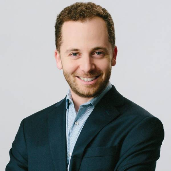 Mitchell Marcus, a white male with brown curly hair and a beard, smiles at the camera. He is wearing a blue sports jacket on top of a blue collared shirt.