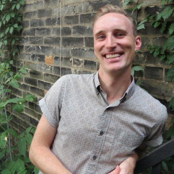 Paul Beauchamp, a white man with short light brown hair smiles at the camera. He is wearing a soft green patterned button-down short sleeves shirt, and is leaning up against an outdoor brick wall with hints of green foliage.