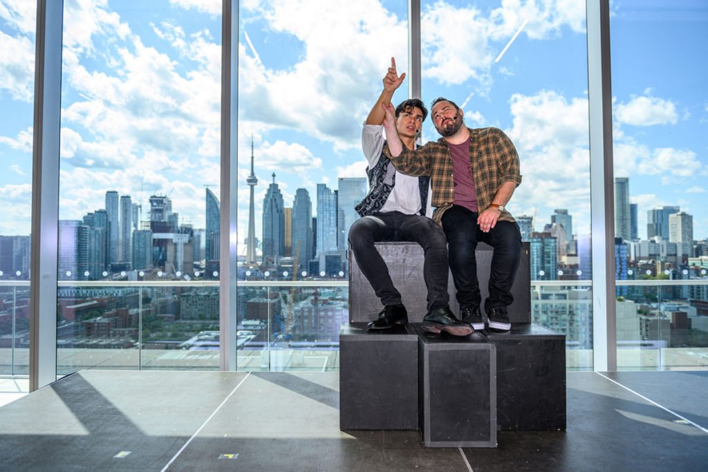 Two men sit huddled together on prop blocks, looking and gesturing at something high out of frame, one arm each, raised up.