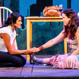 Synthia (left) and Chilina (right), are seated together on a wooden stage floor and in conversation, with a kitchen table and chair in the background. Synthia, a mixed race person with light brown skin and long, brown wavy hair in a loose ponytail, is looking at Chilina, kneeling and holding Chilina's right hand. She is wearing a white blouse and dark blue pants. Chilina, a pale skinned woman with dark brown eyes and chestnut hair, is looking intently at Synthia, one leg sprawled out. She is wearing a boho outfit of a striped tank top, pink skirt, tied shawl and bangles.