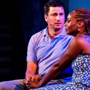 Jonathan (left) and Yemie (right) are seated close together, holding each other's hands tightly between their laps, both looking deep in emotion. Yemie, a Black woman with warm brown eyes and long single boxed braids, is wearing a white and blue patterned dress, a pearl earring highlighted. Jonathan, a white man with short, styled brown hair and blue/grey eyes, wears a blue polo and grey slacks, looking at Yemie as she stares into the distance, tears in her eyes.