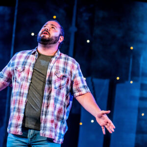 Michael, a white LGBTQ2S+ actor with short dark hair and brown eyes brimming with emotions, looks up into the night sky. He is mid-song, his arms spread, and wearing a plaid open shirt layered over a khaki tee and jeans. The background is dark and foggy, dotted with twinkling lights.