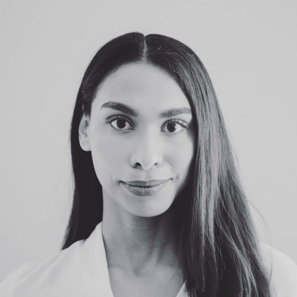 Patricia Cerra is a person of colour who is smiling at the camera in a black and white photo. She is wearing a white shirt with her long dark hair parted down the middle and falling over her left shoulder.