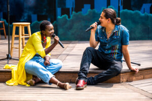 2 performers are singing on an outdoor wooden stage, sitting together. Germaine (left), a dark-skinned Black Femme has their legs slightly crossed, leaning forward. Dillan (right), an Indigenous Ojibwe performer with long, dark hair, leans back & smiles as he sings.