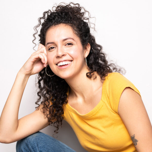 Camila Diaz-Varela smiles widely into the camera and sits comfortably on the floor, while resting their head in their hand. They have long dark brown curly hair that spills from a messy updo, dark brown eyes, and are wearing a mango coloured shirt and jeans.