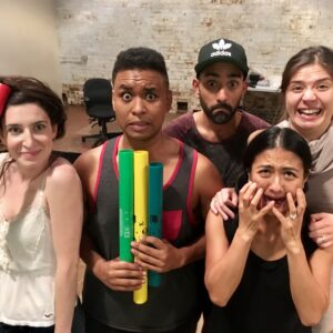 5 people stand huddled together to pose for a silly picture in rehearsals.