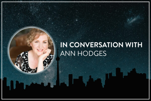 """A background of the Toronto skyline silhouette runs along the bottom, against a blue, star filled galaxy sky. Centered is a circular headshot and text. The headshot is a smiling white woman (Ann Hodges), with a white glow around the circle edge. Bold white text to the right of the image reads, """"In conversation with / Ann Hodges."""""""