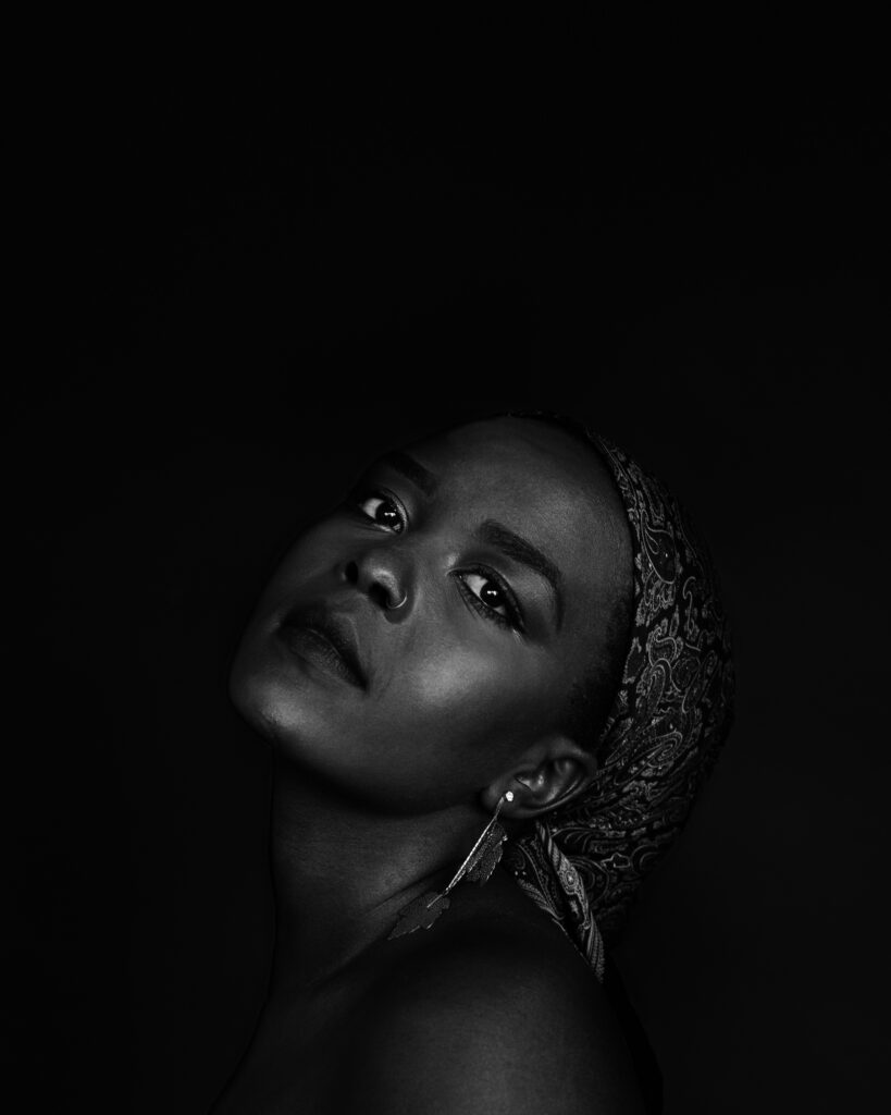 A black and white photo of Germaine Konji, a dark skinned Black Femme in her mid twenties with warm brown eyes and black hair wrapped in a patterned headscarf. She's looking meaningfully at the camera, dignified against the black background with her head tilted back.