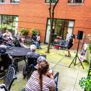A wide shot of a patio concert at an elderly care home, with a group of residents (and a few caretakers) in assorted chairs/wheelchairs watching. Brittany Miranda (right) is standing in a black dress, mask, and heels, singing into a standing mic between two speakers. The building's red brick wall and tall windows are the backdrop.