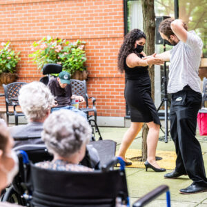 Multiple residents are gathered on an outdoor patio of a care home, seated and watching 2 performers mid-dance, holding each other's forearms. Brittany (left) is a mixed race artist with big, curly brown hair and a black dress on. Samuel (right) is a white artist with long hair pulled into a bun, and wearing black pants and a white patterned button up.