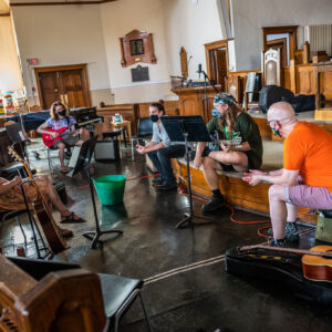5 white artists are seated in a distanced group, inside an empty church, with a wooden stage, pews and decor in the background. 4 of them are looking at the person seated in centre frame, and they speak. Everyone is wearing face masks with varying designs, and handling or next to a guitar of their own.