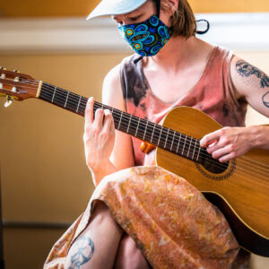 A close up of a white femme musician seated and looking down at their acoustic guitar, mid-strum. They're in a soft lit room, and wearing a pattern blue mask with a sleeveless top and skirt, showing their tattoos.