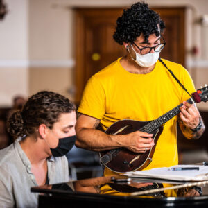 2 masc presenting musicians are looking down at their sheet music. Left; a white musician is seated at a baby grand piano, and wearing a simple black mask, their curly hair in a bun. Right; a tall musician is standing and playing a lute, while wearing a plain white mask and hair short curly hair and black glasses.