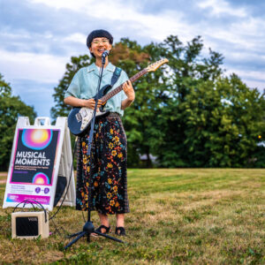 """Vicky Wang is standing in an open field of brown and green grass, smiling at the camera. She's holding an electric guitar, plugged into a mini amp to her left, smiling behind a standing mic. Behind her (left) is a white sandwich board with graphics and large font reading, """"MUSICAL MOMENTS."""" In the distance is a tall tree line and a blue sky with wispy clouds."""