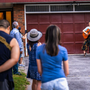 An image of a handful of people standing along the walkway and in front of a red bricked home and driveway, their backs to the camera and facing Vicky (right). Vicky Wang is standing on the driveway, smiling at the camera while singing and playing her acoustic guitar.