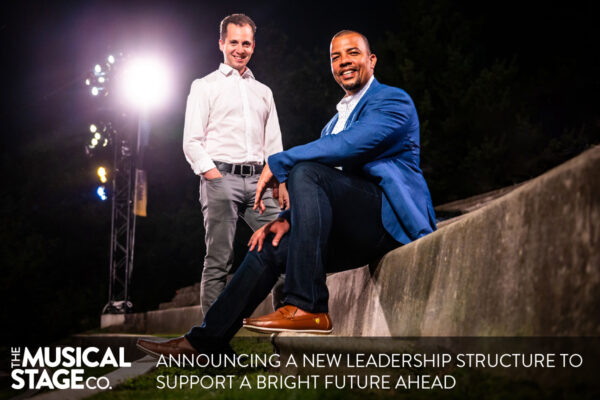 """Two men are posed outdoors on tall concrete amphitheatre seats at night, with bright outdoor overhead lighting. Mitchell (left) is a white man with brown curly hair, standing and smiling at the camera. He is wearing a white dress shirt and grey pants. Ray (right) a Black man with close cropped black hair, a widow's peak, dark eyebrows and a goatee, sits centre, with one knee bent, smiling at the camera. He is wearing a blue blazer, white shirt and dark wash jeans. White text along the bottom reads, """"Announcing a new leadership structure to support a bright future ahead."""" The Musical Stage Company logo in white sits to the left of the text."""