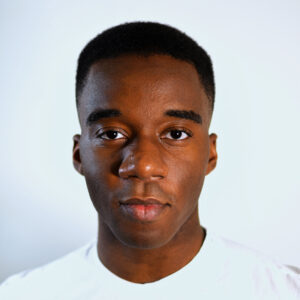 Matthew Joseph (he/they), a black non-binary artist with dark brown eyes and a fade, delivers a warm but subtle smirk to the camera. He is wearing a white crew neck shirt and standing against an eggshell white background.