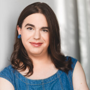 Avery Jean Brennan, a white Transfeminine person with dark brown eyes and long brown hair smiles at the camera. They are wearing blue circular earrings and a blue denim dress. They are standing in front of a white backdrop with their arms folded across their chest, and their nails are painted bright purple.