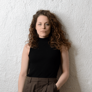 Kaylee Harwood, a caucasian woman with long curly brown hair, stands on one foot against a cream wall, holding reading glasses while looking at the camera. She is wearing a sleeveless, black turtleneck, and brown trousers and has one hand in her pocket.
