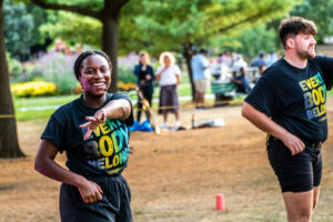 A shot of two instructors in matching t-shirts and black shorts outside at a park - mid dance move as they lead a dance class. Left, a Black femme instructor with a mini head-mic, smiles at the camera, their left arm reaching across their body. Right, a white masc instructor looks out of frame as they dance. Park goers mill in the background.