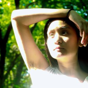 Maddie Bautista is a queer Filipina in her mid-twenties, with brown skin and long, straight black hair. She has one arm raised above her forehead to protect herself from the sun, which is shining directly at her. Her eyes are looking above the horizon and off the camera, and there is lush, green foliage behind her, dappled with sunlight.